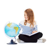 Child looking at globe and holding book — Stock Photo