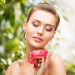 Woman with diamond earrings, ring and flower — Stock Photo