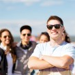 Teenager in shades outside with friends — Stock Photo