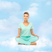 Girl sitting in lotus position and meditating — Stock Photo