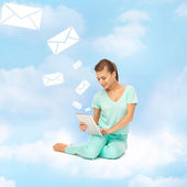 Woman sitting on the cloud with tablet pc — Stock Photo