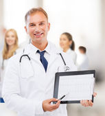 Male doctor with stethoscope showing cardiogram — Stock Photo
