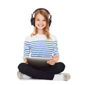 Child with headphones and tablet pc — Stock Photo