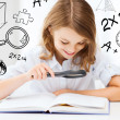 Girl reading book with magnifier at school — Stock Photo #30594821