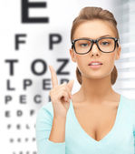 Woman in eyeglasses with eye chart — Stock Photo