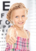 Girl with optical eye chart — Stock Photo