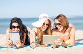 Girls with tablet pc on the beach — Stock Photo