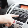 Stock Photo: Man using car audio stereo system