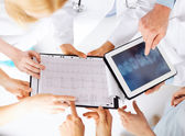 Group of doctors looking at x-ray on tablet pc — Stock Photo