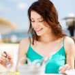 Girl eating in cafe on the beach — 图库照片