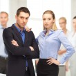 Businessman and businesswoman in the front of team — Stock Photo