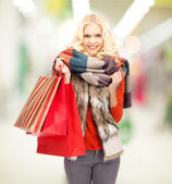 Teenage girl in winter clothes with shopping bags — Stock Photo