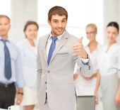 Smiling businessman with thumbs up — Stock Photo