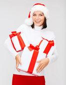 Mujer con sombrero de ayudante de santa con muchas cajas de regalo — Foto de Stock