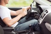 Man drinking coffee while driving the car — Stock Photo