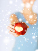 Woman hand holding red apple with heart shape — Stok fotoğraf