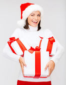 Winking woman in santa hat with many gift boxes — Stock Photo