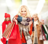 Teenage girls in winter clothes with shopping bags — Stock Photo
