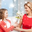 Happy mother and daughter with flowers — Stock Photo #31664805