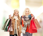 Women in winter clothes with shopping bags — Stock Photo