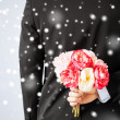Stock Photo: Man hiding bouquet of flowers
