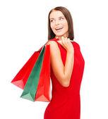 Femme en robe rouge avec des sacs à provisions — Photo