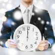 Man holding wall clock showing 12 — Stock Photo