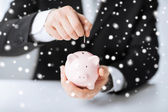 Man putting coin into small piggy bank — Stock Photo