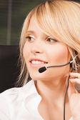Female helpline operator with headphones — Stock Photo