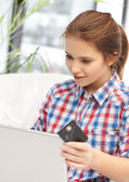 Happy teenage girl with laptop and credit card — Stock Photo