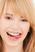 Teenage girl sticking out her tongue — Stock Photo