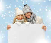 Couple in a winter clothes holding blank board — Stock Photo