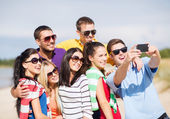 Group of friends taking picture with smartphone — Stockfoto