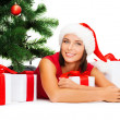 Smiling woman in santa helper hat with gift boxes — Stockfoto