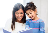Mother and daughter with book — Stockfoto