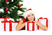 Smiling woman in santa helper hat with gift boxes — Stock Photo