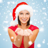 Woman in santa helper hat with something on palms — Stock Photo