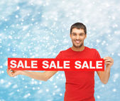 Smiling man in red shirt with sale sign — Stock Photo