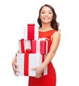 Uśmiechnięta kobieta w czerwonej sukience z wielu prezentowe — Zdjęcie stockowe