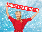 Smiling woman in red dress with sale sign — Stock Photo