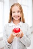 Beautiful teenage girl showing red heart — Stock Photo
