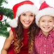Happy mother and child boy in santa helper hats — Stock Photo #32490671