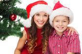 Happy mother and child boy in santa helper hats — Stock Photo