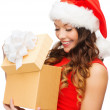 Smiling woman in santa helper hat with gift box — Stock Photo #32513115