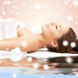 Woman in spa salon lying on the massage desk — Stock Photo #32677079
