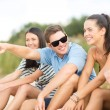 Group of friends pointing somewhere on the beach — Foto Stock
