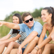 Group of friends pointing somewhere on the beach — Foto de Stock