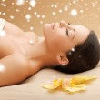 Woman in spa salon lying on the massage desk — Stock Photo #32678311