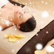 Woman in spa salon lying on the massage desk — Stock Photo #32678329