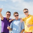 Friends on the beach with bottles of drink — Stock Photo #32678675